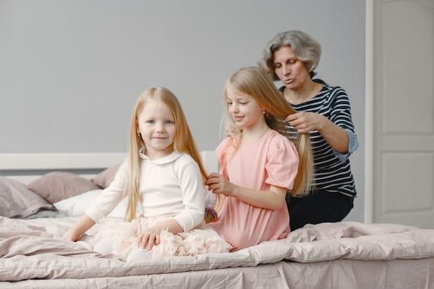 Oma vlecht het haar van kleindochter. tweede kleindochter vlecht zus. gezellig huis, familierelaties.