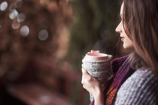 Oman draagt warme gebreide kleding buiten het drinken van een kop hete thee of koffie