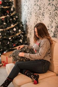 Oman in sweater met de kroon van kerstmis dichtbij verfraaide spar