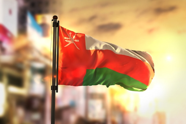 Oman vlag tegen stad wazige achtergrond bij zonsopgang achtergrondverlichting