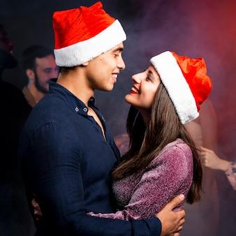 Omarmd paar kerst hoeden dragen