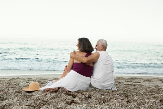 Omarmd senior koppel genietend van hun dag op het strand