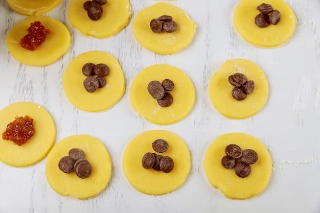 Omcirkel zandkoekdeegkoekjes met chocoladeschilfers die zijn voorbereid voor het bakken.