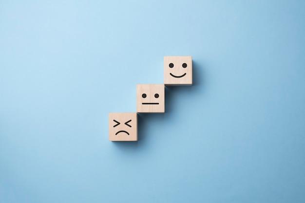 Omdraaien van houten kubusblok van verdrietig naar glimlachemotie op blauw