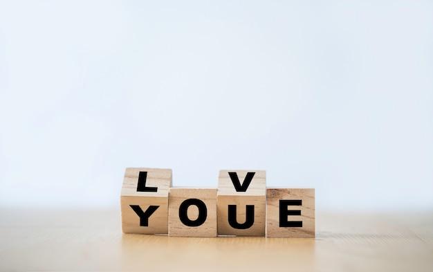 Omdraaiende houten blokkubus die op het scherm wordt afgedrukt, hou van je formulering. valentijnsdag concept.