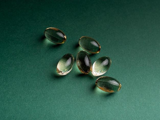 Omega 3 capsules die geïsoleerd op een groene achtergrond liggen