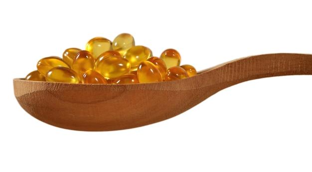 Omega-3 visvetoliecapsules in houten lepel op een witte achtergrond