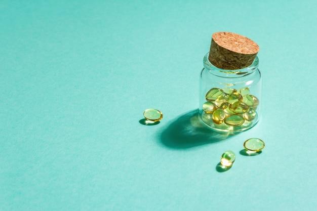 Omega3 tabletten in een oude fles op een turquoise mat.