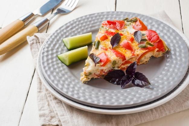 Omelet die met groenten op een plaat op een witte houten lijst dient