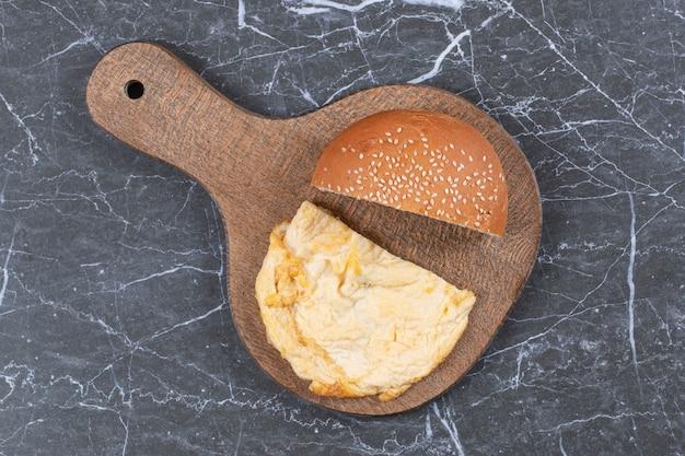 Omelet en gesneden broodje op de snijplank.