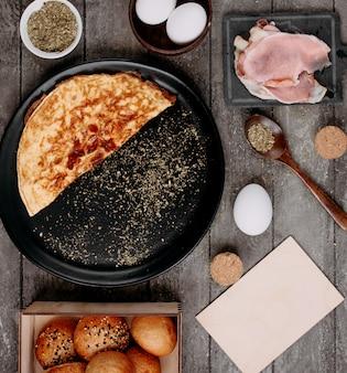 Omelet in de pan en rauwe bacon aan de zijkant