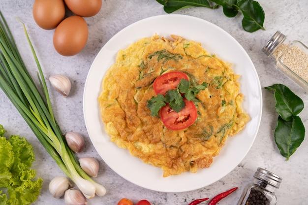 Omelet in een wit bord gegarneerd met tomaten en koriander.