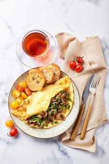 Omelet met champignons en peterselie in plaat op marmeren achtergrond. frittata - italiaanse omelet voor ontbijt of lunch. plat leggen. bovenaanzicht, overhead, kopieerruimte