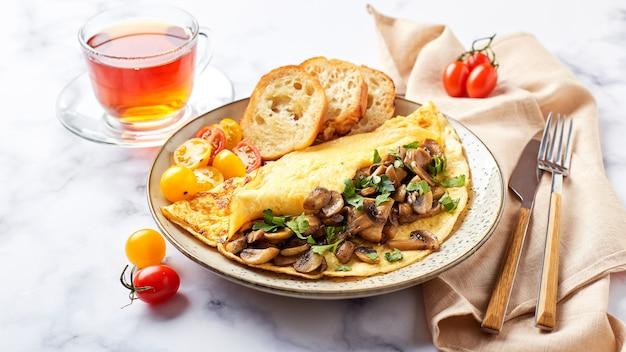 Omelet met champignons en peterselie in plaat op marmeren achtergrond. frittata - italiaanse omelet voor ontbijt of lunch.