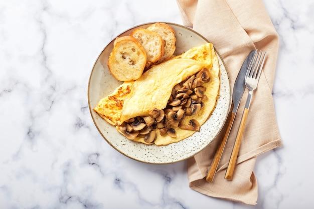 Omelet met champignons in plaat op marmeren achtergrond. frittata - italiaanse omelet voor ontbijt of lunch. plat leggen. bovenaanzicht, overhead, kopieerruimte