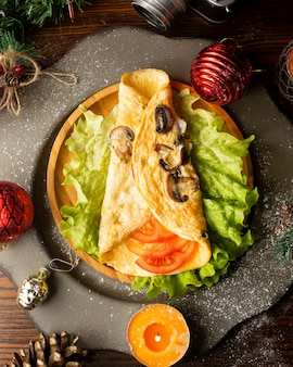 Omelet met champignons op sla gelegd en om plakjes tomaat gewikkeld