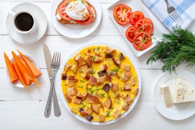 Omelet met geroosterde sneetjes brood en tomaten, wortelen, kopje koffie rond op witte houten tafel
