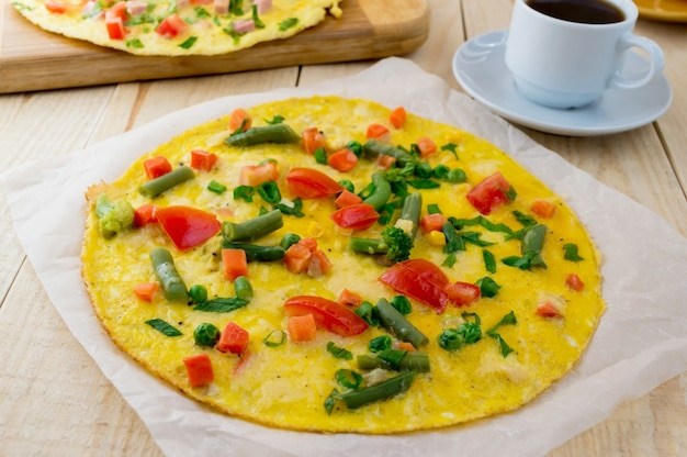 Omelet met groenten op een houten achtergrond, en een kopje koffie. ontbijt