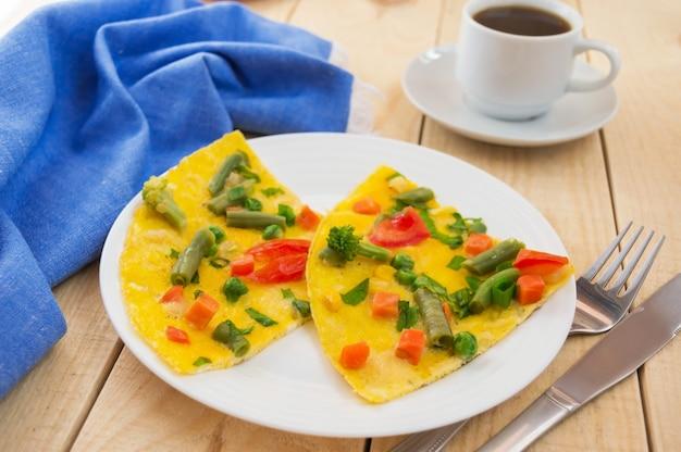 Omelet met groenten op een houten achtergrond, en een kopje koffie. ontbijt.