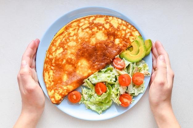 Omelet met groenten op een plaat. blauwe plaat. uitzicht van boven. omelet met groenten op een plaat die voor ontbijt wordt gediend. uitzicht van boven