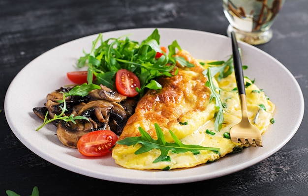 Omelet met kaas, groene kruiden en gebakken champignons op plaat. frittata - italiaanse omelet