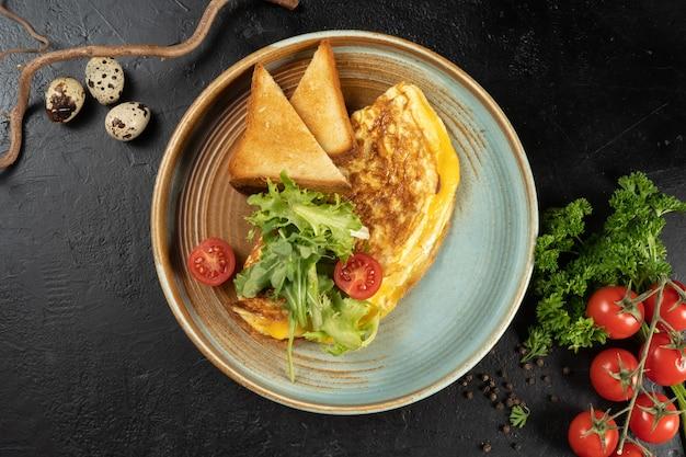 Omelet met kaas, salade en cherrytomaatjes.