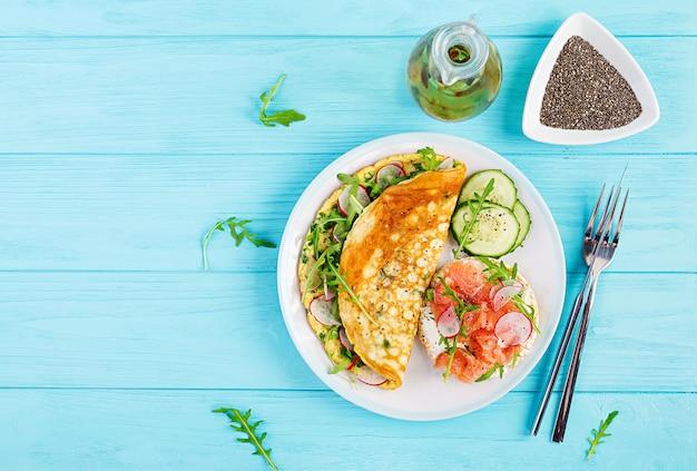 Omelet met radijs, groene rucola en sandwich met zalm op witte plaat
