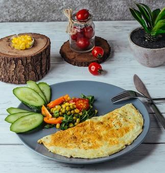 Omelet met salade van komkommer, tomaat, maïs en kruiden in rustieke stijl