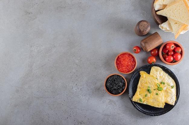 Omelet met sneetjes brood en rode en zwarte kaviaar.