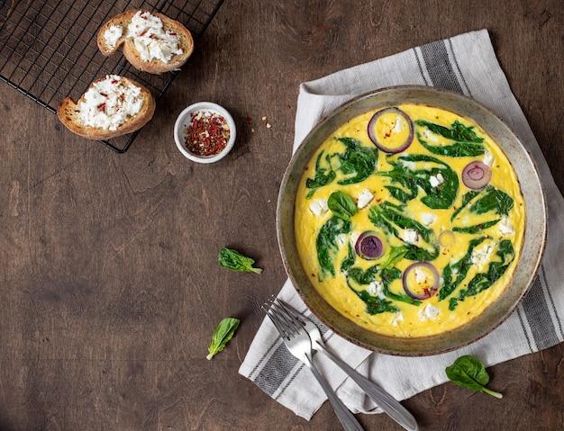Omelet met spinazie en feta-kaas in een ijzeren pan op een houten, rustiek. bovenaanzicht copyspace