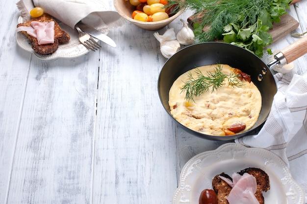 Omelet met tomaat in een koekenpan voor ontbijt, kaas en greens op een witte houten achtergrond