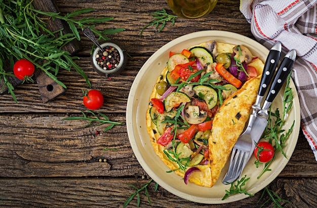 Omelet met tomaten, courgette en champignons. omelet ontbijt. gezond eten. bovenaanzicht plat leggen