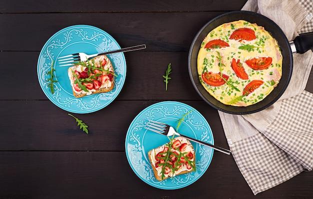 Omelet met tomaten, ham, groene ui en sandwich met aardbei op donkere tafel, bovenaanzicht