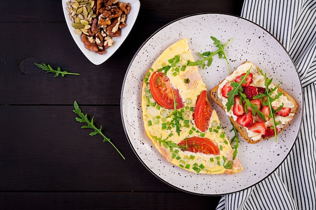 Omelet met tomaten, ham, groene ui en sandwich met aardbei op donkere tafel