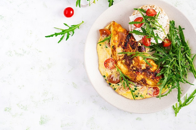 Omelet met tomaten, kaas en groene kruiden op plaat. frittata - italiaanse omelet. bovenaanzicht, overhead, kopieerruimte