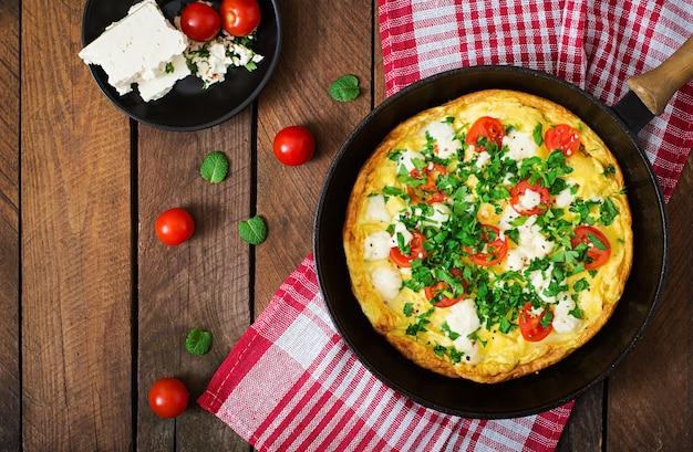 Omelet met tomaten, peterselie en feta-kaas in de pan. bovenaanzicht