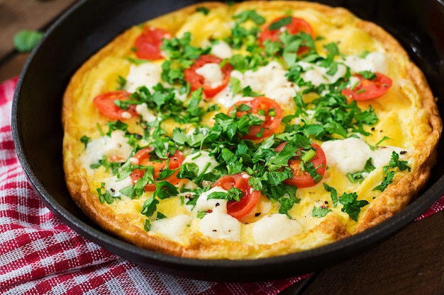 Omelet met tomaten, peterselie en feta-kaas in de pan