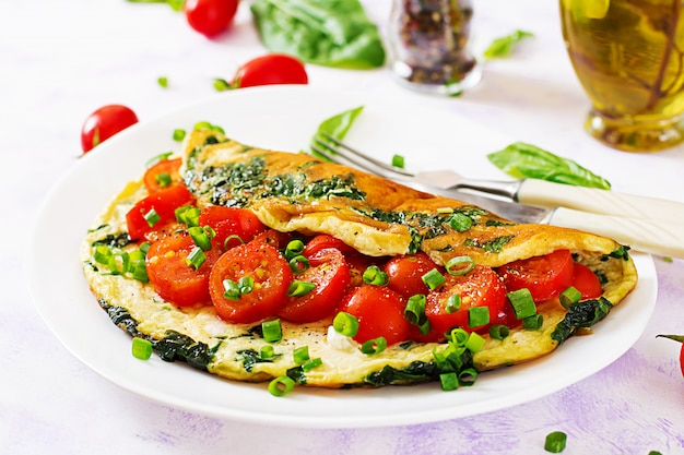 Omelet met tomaten, spinazie en groene ui op witte plaat.