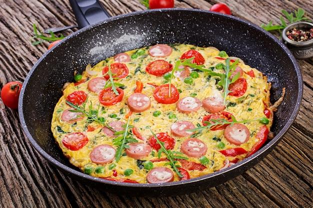 Omelet met tomaten, worst en groene erwten in rustieke stijl
