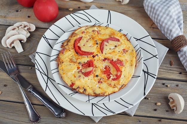 Omelet met ui, tomaten en champignons in mooie witte borden
