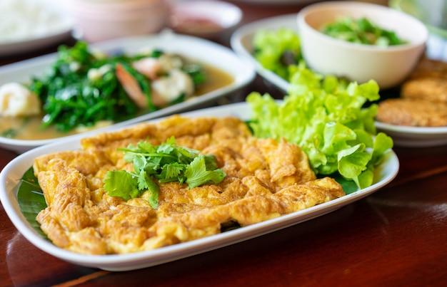 Omelet (omelet, scrambled) met groene koriander in witte schotel op houten tafel