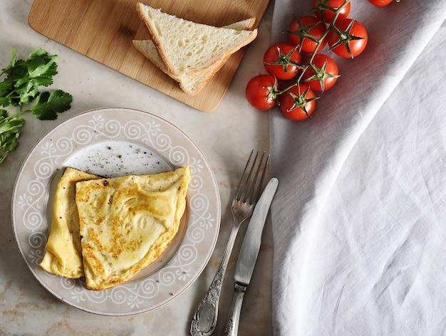 Omelet op een bord, peterselie, tomaten, toast