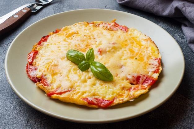 Omelet, roerei met tomaten en kaas in een bord op een donkere tafel.