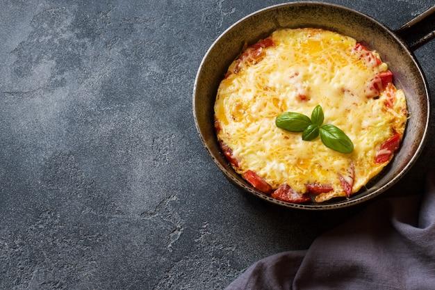 Omelet, roerei met tomaten en kaas in een pan op een donkere tafel.