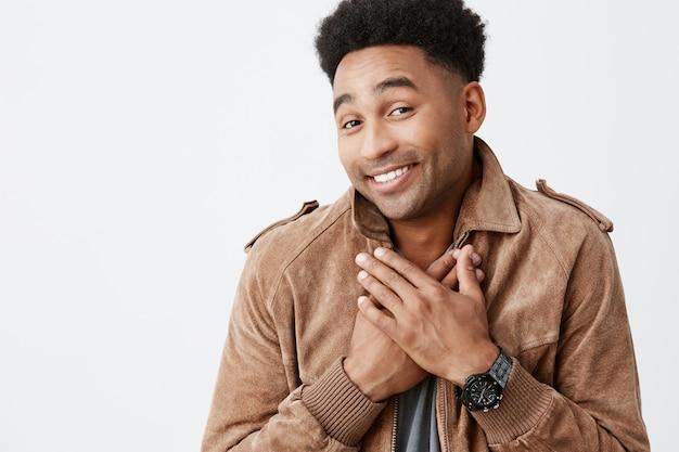 Omg. dit is zo lief, dank je. portret van mooie vrolijke afro-amerikaanse man met krullend haar gelukkig nadat vriendin hem cadeau gaf voor hun jubileum samen. positieve emoties