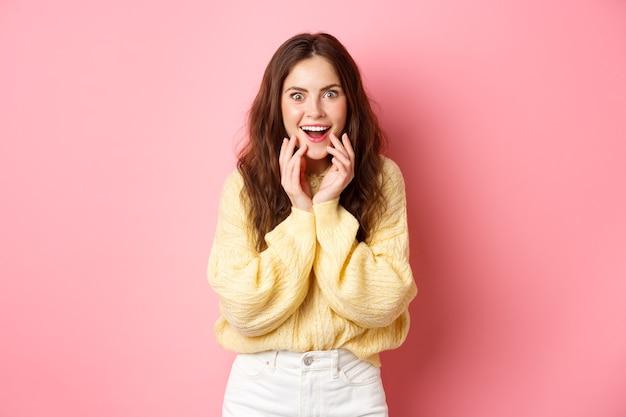 Omg echt. opgewonden jonge vrouw hoort roddels of supergoed nieuws, verbaasd starend, glimlachend en hand in hand op het gezicht, luister naar interessante geruchten, staande over roze muur.