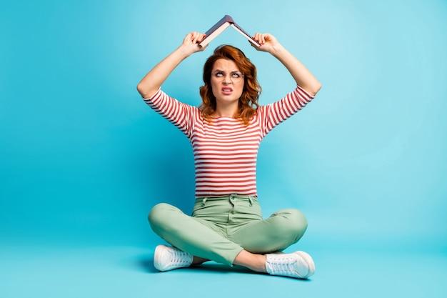 Omg examenvoorbereiding weer! foto van het hele lichaam van boos vrouw zitten gekruiste benen kijken boven het hoofd houden papieren boek afkeer van haar encyclopedie dragen groene stijlvolle outfit geïsoleerde blauwe kleur