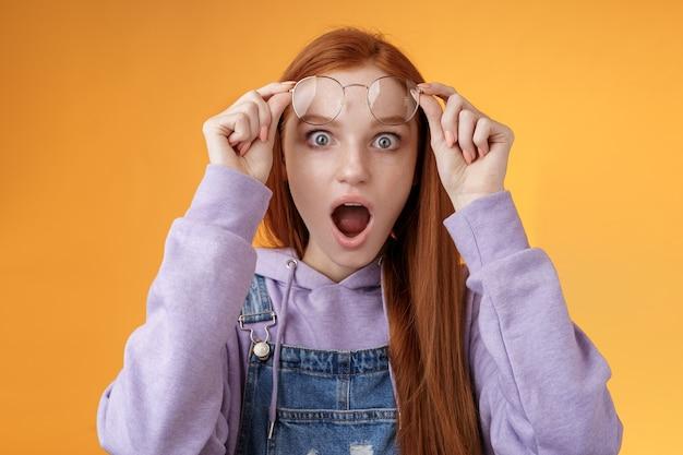 Omg geen gekke manier. geschokt emotionele roodharige vriendin opstijgen bril sprakeloos drop kaak hijgen verbijsterd grote ogen camera staren verbaasd ontdekte schudde geheime staande oranje achtergrond.