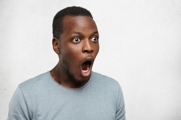 Omg. half profiel shot van grappige jonge zwarte man met open ogen die voor zich uit kijkt met wijd opengesperde mond en opengevallen mond, zijn hele blik die een schok en vol ongeloof uitdrukt
