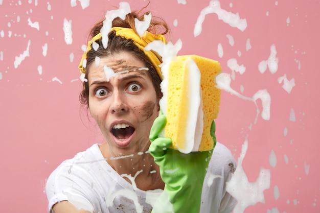 Omg. headshot van emotionele huisvrouw met vuil gezicht raam wassen met spons en chemicaliën, geschokt voelen als ze alles zelf moet schoonmaken, kijkend, mond wijd openhoudend
